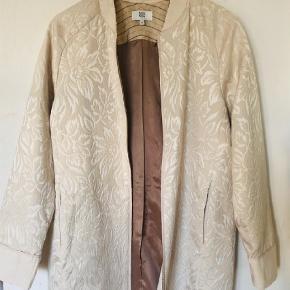 Smuk jakke/frakke i blomstret jacquardmønster med lommer og lynlås og uden krave. Aldrig brugt. Let foret.