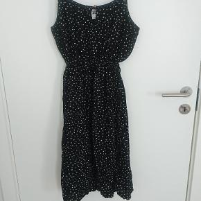 Sort kjole med hvide prikker.  87 cm lang. Kan spændes ind under brystet.