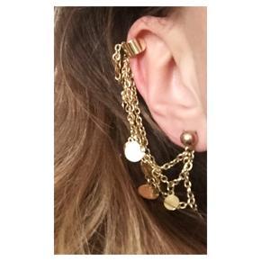 Guldfarvet ørering med cuff. Kuglen sættes i øret og cuff'en sættes længere oppe på øret så kæderne hænger langs øret. Sender gerne med DAO :)