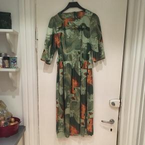 Hjemmesyet vintage kjole i glat kunststof. Grønne og orange farver. Super elegant. Passer en str 38. Mål: længde: 108 cm, bryst; 2*40 cm. Talje; 2*38 cm. Der er lidt elastin i stoffet, så kjolen giver sig lidt.