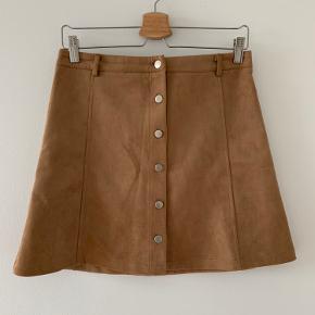 Sælger denne brune nederdel fra Neo Noir i str S. Den er kun blevet prøvet og ellers har den bare ligget i skabet.   Materialet er dejlig blødt og den har knapper foran.