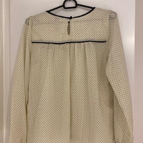 En elegant og flot bluse i de fineste polka-prikkee fra H&M. Str. 36, men kan sagtens bæres af en M. Brugt een gang.  Kan afhentes i Vejle eller sendes på købers regning.