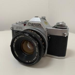 """Sælger dette meget flotte og populære """"Canon AV-1"""" 35mm film kamera inkl. et Canon FD 50mm F1.8 objektiv. Eneste det fejler er at Objektive har fået et lille han foran, men har kun kosmetisk betydning, så det er stadig funktionsdygtig."""