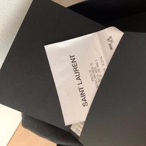 """HELT NY kortholder fra Saint Laurent i sort """"smooth leather"""", med lynlås og 5 kortlommer.  Mål: 13 x 8 x 0.5 CM  Nypris: 195 euro = 1500 kroner  STYLE ID: 458583C150J1000 Made in Italy  Pungen har kun været pakket ud for at tage billeder. Aldrig brugt og ALT medfølger: Kvittering, dustbag, æske, diverse ekstra ting fra YSL butikken.  Jeg har fået den i gave, men det er ikke den jeg ønsker mig. Sælger derfor kun, med mindre du vil bytte med en kortholder i lædertypen """"Grain de poudre""""."""