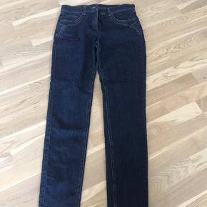 """Lækre og super flotte jeans fra LauRie i str 38  Det er modellen """"Jane"""" og de er slim fit.  Fejlkøb, sælges derfor uden at være brugt. Kun prøvet på. Standen er derfor som ny.   """"""""""""Disse super komfortable 5-pocket jeans er fremstillet af denim med komfort stretch. De har fast linning og lommer foran og bagpå, hvilket er med til at give dem det helt rigtige jeanslook. Denne model har en smal silhuet, der giver facon til den firkantede figur og fremhæver timeglasfigurens former. Bukserne har små pyntestikninger på baglommerne samt ved lommerne foran. Prøv dem og mærk forskellen. LauRies patenterede Magic Slim teknologi flader maven og løfter bagen, så kvindekroppens former fremhæves og får en slankere fremtoning. De er en sikker vinder i enhver garderobe, da de med deres klassiske snit og jeansfarve kan redde ethvert outfit. Alt tøj fra LauRie er Oeko-Tex certificeret, hvilket betyder, at LauRies tøjkollektioner ikke indeholder kræft- eller allergifremkaldende kemikalier. Med andre ord er du garanteret, at tøj fra LauRie er fri for sundhedsskadelige stoffer. Slim silhuet."""""""""""""""