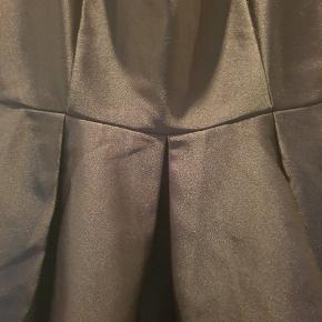 Kjole med masser af vidde i skørtet. Skrålommer og lynlås bagpå. Silkesatin look.