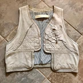 Skøn kort vest i lammeskind. Søde, fine detaljer 👍🏻 så fin over en hvid skjorte eller en grå stram bluse ☺️☺️  Se også alle mine andre annoncer 💃💃  Byd!