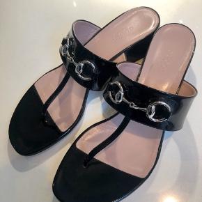 Gucci sandaler - kun prøvet indendørs. Sort lak med sølvfarvede logo bidsler. 4 cm blok hæl.