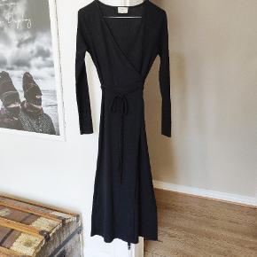Fin slå-om-kjole i vintage 70'er-stil. Ribbet polyester. Jeg er en XS-S og passer den fint. Der står M i mærket, men pga. pasformen vil jeg vurdere at flere størrelser sagtens kan passe den.