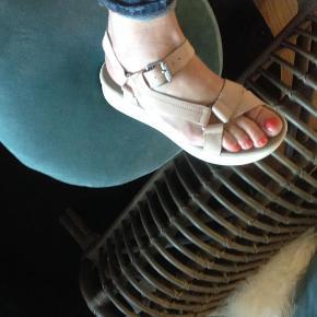 Varetype: Sandaler Farve: Nude Oprindelig købspris: 1099 kr. Prisen angivet er inklusiv forsendelse.  Super skønne og behagelige sandaler. Skal du på storbys ferie eller bare trave meget her til sommer, er disse uundværlige i kufferten.. sidder godt på foden og er vildt behagelige at gå i.  Sendes billigst muligt med DAO