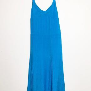 Yderstoffet er 100% silke og inderkjolen er 100% viskose. Den måler omkring 103 cm i længden fra armhulen og ned.