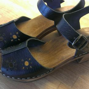 """Brand: Euroclogs Varetype: træsko sandaler clogs Størrelse: 41 (40) Farve: Sort Oprindelig købspris: 600 kr.  GENOPRETTET MED NY PRIS: NU KUN 200 KR PLUS PORTO:  Helt nye sko til en tredjedel af prisen:  Flotte sko/sandaler/træsko fra det svenske mærke Euroclogs. Med fint hulmønster.  Jeg har angivet dem som str 41(40) fordi jeg synes de er ret små i det. Jeg er faktisk str. 40 i de fleste sko (endda nogen gange 39 i åbne sandaler), men træskoene hér er meget smalle i det, og jeg har en ret bred fod. Jeg har derfor også erkendt, at de ER for smalle til mig.  Et par mål på sandalerne:   Længden er en anelse over 26 cm (min fod er 25 cm lang og jeg bruger normalt 39-40 i åbne sandaler). Bredden fortil (under læderet med hulmønster) er en anelse mere end 8 cm (og da min forfod er 10 cm på det bredeste sted, er det klart, at de klemmer mig lidt).  Har kun prøvet at tage dem på herhjemme. Men det går ikke og de må videre ud i verden!  Sælges nu for kun 200 kr. plus porto (45 kr. som forsikret TS-pakke med DAO).  PS: Sandalerne her minder vildt meget om de der """"Svenske Har-Været"""" (må nok ikke nævne mærket hér uden at få bøvl med TS); de koster bare kun det halve - og hos mig en fjerdedel (-;  --- 0 ---  Se også de andre 10-15 lækre par sko, støvler og sandaler, jeg sælger (-:"""