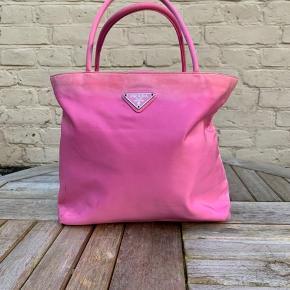 Lækker pink Prada skuldertaske Tasken har tegn på patina. Tasken kommer med autencitetskort, hvilket medfører gratis reparationer i Prada butikken.