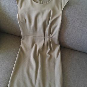 Lækker kjole fra Tiger of Sweden i behageligt stretch jersey. Den passer perfekt i den pæne arbejdsgarderobe. Kjolen er brunlig og rimelig tætsiddende med fin detalje i den ene side af taljen. Kjolen går til midt på låret. Kan evt. afhentes på Frb.