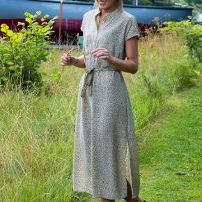 Helt ny og ubrugt, kjolen har korte ærmer, kinakrave og knapper ned langs fronten. Kan bindes med et bindebånd, der giver et flatterende snit.