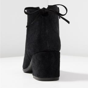 Ankelstøvler med blokhæl i ruskind med fine detaljer.