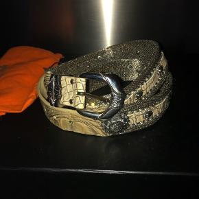 Mrk: Nanni ( italiensk varemærke) meget smukt metalbælte med beige præget læder, str 80 cm pyntet med hvide similistene Der er 1 sten som mangler ellers fremstår bæltet som nyt - ingen tegn på slitage  Med dustbag  #30dayssellout