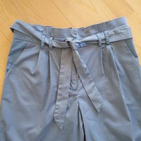 Flot himmelblå farve. Bukser er en kort model med 'paperbag' talje, stofbelt og opsmøg i bomuld. Brugt nogle få gang. Størrelsen passer til en 38. Taljen 78cm i omkreds Invendig benlængde 78cm