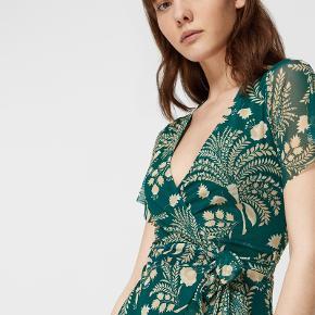 Smuk wrap / slå-om kjole i grøn med beige / støvet gule blomster med bindebånd. Str. S / 36. Normal i størrelsen. Kun prøvet på. Går mig til lige under knæet, jeg er 158 cm. Spørg endelig for flere billeder.