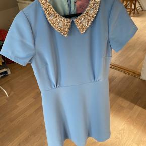 Smuk figursyet kjole fra Edith & Ella i lækker polyester med fint for. A-facon og rundskåret i længde til knæet. Fine pailletter og perler på kraven og lynlåslukning med hægte bagpå. kun brugt få gange