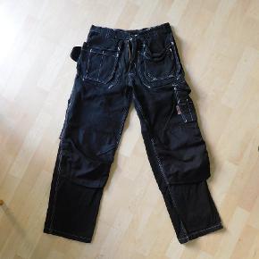 Maxline arbejdsbukser (håndværker bukser) STR. 46 står inden i  Bukser er helt fine stand, der er kun et par syninger i lommerne, som er lidt slidte.