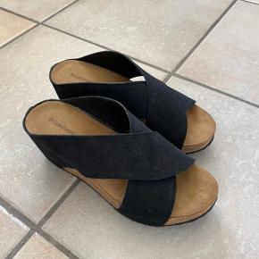 Super fed sandal i lækkert ruskind med kilehæl af kork. Der er 4mm latexskum i sålen, hvilket til sammen gør, at sandalen er super behagelig at gå i og aflaster foden.  Flot stand.  Kun brugt 1 gang, derfor flot stand.