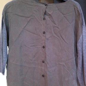 Varetype: bluse Farve: Grå Oprindelig købspris: 600 kr.  Lækker bluse i fint strik og cupro. Knapperne sidder bagpå!  Forsiden (knit): 40% polyester, 30% linen, 20% model, 10% silke Bagsiden: 60% cupro, 40% viscose  Bytter ikke!