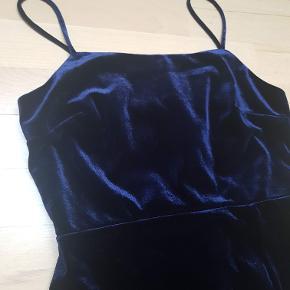 Mørkeblå velourkjole fra mærke Mahina, købt på Hawaii. Brugt ganske få gange.  Kjolen går til midt på låret (er 168 cm). Rigtig flot velour i god kvalitet. Lille slids i siden og for i hele kjolen. Ingen synlig slitage.