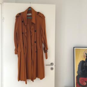 """Fin orange trenchcoat fra ZARA. Den er i brugt, men i god stand. Dog er stoffet lidt """"nusset"""" nogle steder på jakken. Bytter ikke"""
