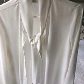 Fin bluse med bindebånd i halsen. Meget lækker og elegant.  Viscose/polyester-mix. Ikke gennemsigtig.