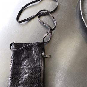 Super lækker lille taske / pung i ægte slangeskind fra danske Carlend. Farven ligger et sted mellem mørkebrun og sort. Nypris 1000,-.