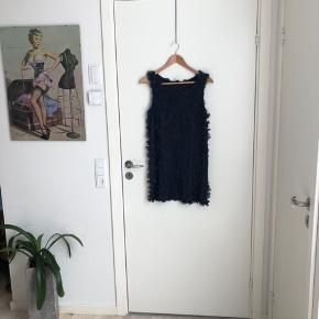 Skøn kjole med blomster applikationer i marineblå farve. Den går til midt låret (jeg er 168). Den er så fin. Jeg kan ikke passe den mere