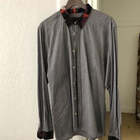 Grå Junk deluxe skjorte str XL. Som har lidt mønster på krave og folde ærmerBrugt få gange  Kan hentes i Vejle eller Århus eller sendes på købers regning