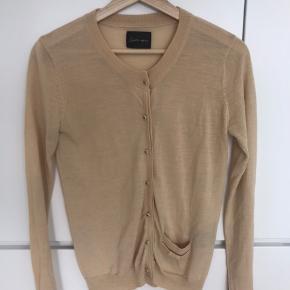 Smuk cardigan i lys brun med fine stjerne knapper. Lavet af 50% uld og 50% akryl.