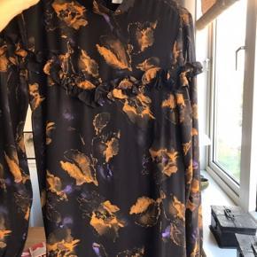 Kjolen er ikke brugt, men er super yndig med 'flæse' detaljer og blomster. Modellen hedder Carola dress i maxi / lang.. Bælte til om livet medfølger i samme mønster