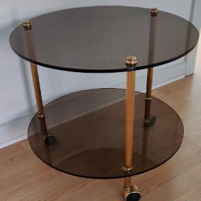 Retro 1960'er bord i messing og røgfarvet glas. Bordet har originale messing hjul og ingen skader Højde 43 cm og dybde ca 50 cm.