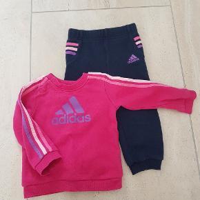 Adidas joggingsæt str 80. Mørkeblå bukser med bindebånd, striberne fortsætter om bagpå. Ingen krak i tryk. Brugt men står næsten som nyt.