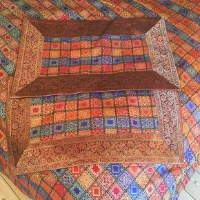 Stort smukt håndlavet (senge)tæppe i silke fra Rajasthan. Mørk rødt med fine vævede mønstre i guld, kongeblåt og sort. 270 x 225 cm. Bred mørkrød kant med mønster vævet i guld. Blød, rød silke på bagsiden. 2 pude covers 40x65 cm følger med. Nyt og aldrig brugt.