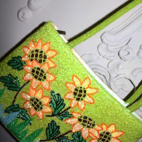- BENYT 'KØB NU' FUNKTIONEN, VED KØB -  Cool perlebesat lysegrøn håndtaske med hank. Tasken har et udvendigt sommerligt solsikkemotiv af perler og palietter, er foret med grønt satinstof indvendigt og har en indre sidelomme. Den har en lynlåslukning øverst og kan lukkes fuldstændigt til.  ○ Mærke: Ukendt - intet indvendigt mærke ○ Størrelse: One Size - Bredde: 30 centimeter - Højde uden hank: 20 centimeter - Højde med hank: 43 centimeter  - Dybde: 5,5 centimeter  ○ Stand: Næsten som ny ○ Fejl/Mangler: Har lette overfladiske pletter inde i foret  ○ Materiale: Udvendigt: Diverse perler og palietter / Indvendigt: Satin