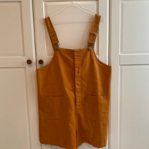 Cool playsuit/dungaree fra Monki i brændt gul/orange farve med to lommer foran og ingen bagpå. Brugt og vasket én gang.