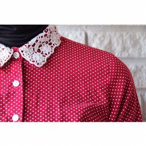 Sød bomulds forårsskjorte i rød med prikker. Blondekraven er en flot detalje, som giver skjorten et ekslusivt udtryk. Kan kombineres med det meste i klædeskabet. Skjorten er aldrig brugt, og fejler intet. Fits 32-34. Pris: 120 kroner.