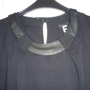 """Flot kjole i gabardine agtig stof i viscose/polyester/elastan. Har """"læder""""bånd rundt i halsen. Har flot ryg. Længde 97 cm."""