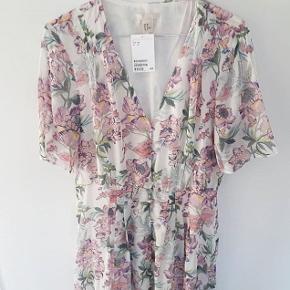 Blomstret maxi kjole fra H&m i en stor str. 38. Med blomsterprint, knapper fra brystet og ned samt underskørt/underkjole. Fremstillet i polyester og viskose. Helt ny og ubrugt, stadig med mærke. Pris: 150 kr plus porto