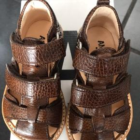 Meget flotte sandaler i mørkecognac  (redbrown)  De passer til en normal til bred fod og har 2 velcrolukning - de er nemme at tage på.  De kommer den orginale kasse.  STR: 21: 13, 6 cm  Passer til en normal/bred fod  Det er fast pris og vi tillader os ikke at svare på bud/bytte.   Normalpris: 850,-  MP 425,- plus fragt