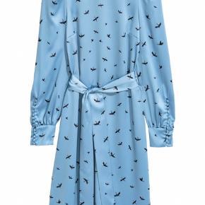 Lyseblå langærmet kjole fra H&M med fugleprint.  Har fin detalje med knapper på ærmerne. Er aldrig blevet brugt. 100% polyester.