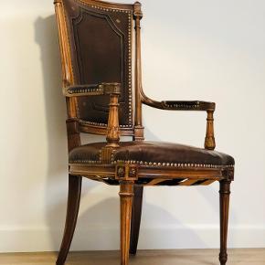 En meget gammel stol med hånd udskæringer og Guldbemalet bord, emblemer samt G F.   Den har nogle ridser i læderen, men alderen taget i betragtning gør den det godt, og man sidder rigtigt godt i den.   Prisen er Fast.