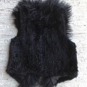Fra MINUS :  Lækker pelsvest i ægte pels. Kanin og lam : kaninpels i selve kroppen og lammeskind i halsudskæring og ned foran til bund. Lammeskindet med længere hår end kaninpels. Lukkes foran med lædersnore. Brugt max et par gange. Oprindelig købespris : 1400,- Sender gerne med DAO på købers regning.