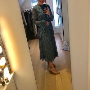 Mellemlang / lang kjole fra gestuz i en smuk blå farve med blomstermønster. Er blevet lagt en smule op og derfor ikke ligeså lang som originalen. Fitter en xs-S