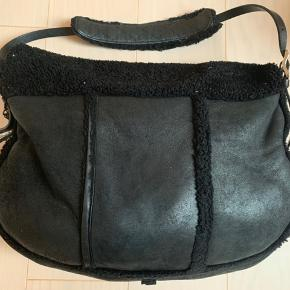 Original Jimmy Choo taske i rulam, model Biker.  Tasken er brugt og har slidmærker, på blandt andet bagsiden af tasken kan ses hvor rulammet er slidt. Det er der hvor tasken har kørt op af mit tøj når jeg har gået med tasken. Ingen skader.  Fortil ses også lidt slid, samt på skulderstroppen hvor rulammet også er slidt lidt.   Sælges billigt eftersom tasken er brugt og som beskrevet med brugsmærker. Se fotos  Tasken har et stort rum som lukkes med lynlås. En åbent rum fortil på tasken. Samt et lille rum med lynlås.  Måler 42x33 cm  Taskens Nypris 15.000 kr.