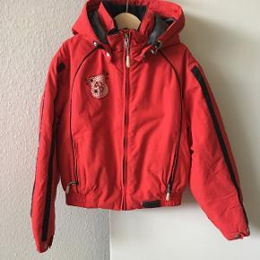 Det er en lille rød sportsjakke til en på 10-11 år og den er fra Brugi (både drenge og piger)